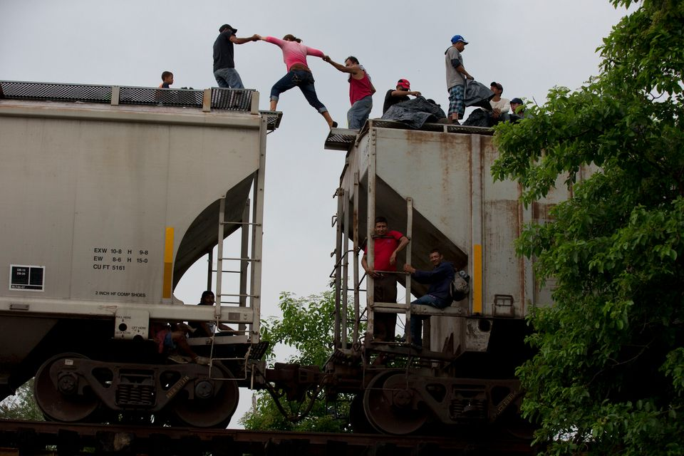 FILE - In this June 20, 2014 file photo, a woman is helped from one boxcar to another, as Central American migrants wait atop