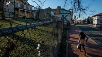 WASHINGTON, DC - JANUARY 17: A pedestrian passes decaying homes in the 2200 block of Martin Luther King Avenue in Washington, DC on January 17, 2014.  The parcel, better known as the 'Big K site' will be the focus a Historic Preservation Board Hearing where the wishes of a developer will be weighed along with desires from people in the community. (Photo by Bonnie Jo Mount/The Washington Post via Getty Images)