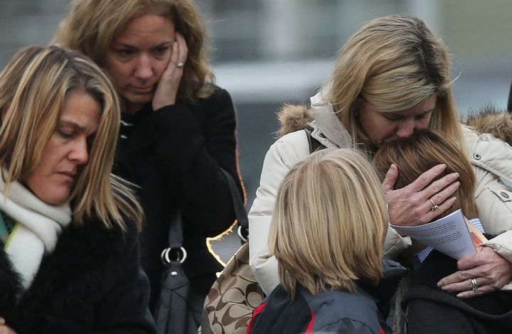 A woman comforts a boy as mourners leave the funeral for 6-year-old Jack Pinto on Dec. 17, 2012 in Newtown, Connecticut.