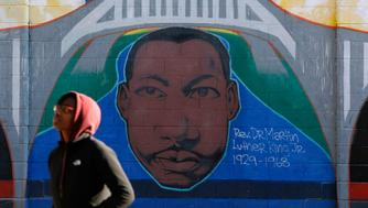 A woman walks past a mural depicting Rev. Martin Luther King Jr. in Selma, Alabama, January 8, 2015.  The town was the scene of a major civil rights confrontation in March, 1965, in which police beat protesters who were marching to demand voting rights for African Americans. Picture taken January 8, 2015.   REUTERS/Jim Young  (UNITED STATES - Tags: ENTERTAINMENT ANNIVERSARY POLITICS)
