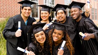 Diverse group of friends dressed in cap and gowns excitedly show off diplomas after college graduation. School building background.