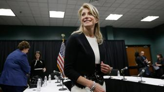 FILE - In this Jan. 9, 2014 file photo, Texas Sen. Wendy Davis smiles as she heads to speak to reporters after an education roundtable meeting in Arlington, Texas. Davis is expected to face Republican Greg Abbott in the Texas governors race. Battleground Texas, a major Democratic effort aimed at turning one of the reddest states blue, will face its first test in the Democratic primary on March 4. (AP Photo/LM Otero)