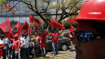 Members of the National Union of Workers of Construction and Similar Industries (SUNTRACS) hold up their flags outside Mossack Fonseca law firm office during a protest in Panama City April 13, 2016. REUTERS/Carlos Jasso