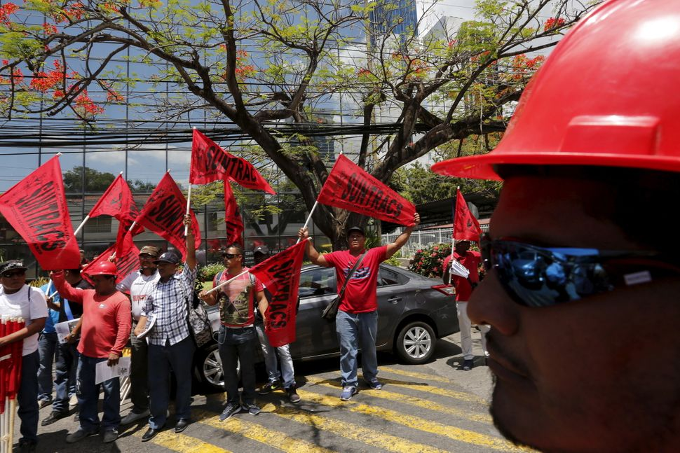 Members of the National Union of Workers of Construction and Similar Industries (SUNTRACS) hold up their flags outside Mossac