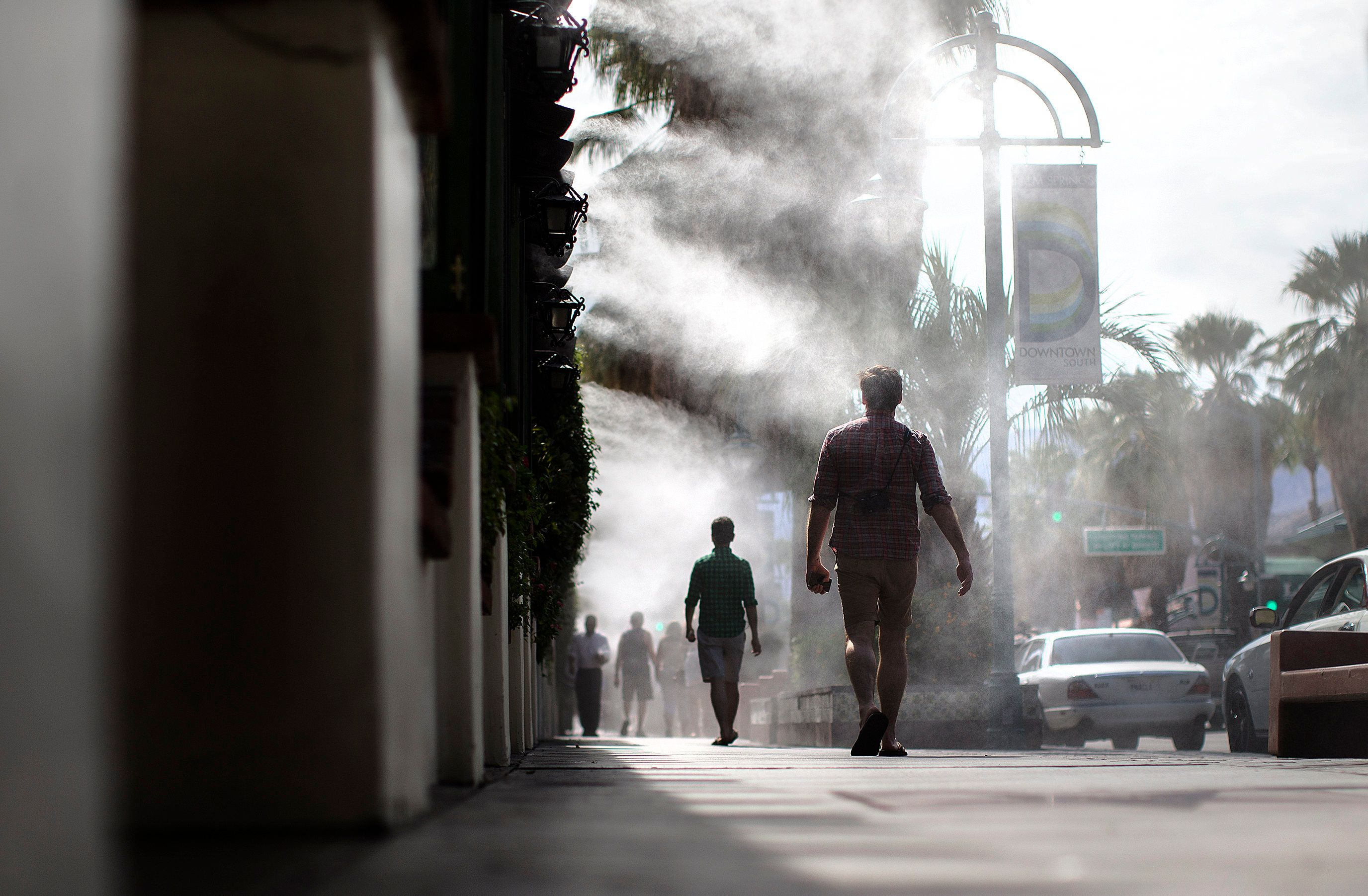 Pedestrians walk under cooling misters in Palm Springs, California, where the temperatures reached the high 90s on Oct. 12, 2