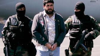 "In this file photo Mexican federal police officers escort Alfredo Beltran Leyva, known as ""El Mochomo"", upon his arrival at the Mexico City's airport, Monday, Jan. 21, 2008. U.S. Bureau of Alcohol, Tobacco, Firearms & Explosive said a .38-caliber Super pistol sold by Phoenix firearms dealer George Iknadosian was recovered in Mexico a year ago when Mexican special forces captured top Sinaloa cartel lieutenant, Leyva. (AP Photo/Eduardo Verdugo, file photo)"