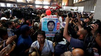 A relative holds a poster of one of the 43 missing students of Ayotzinapa College Raul Isidro Burgos during a catholic service at the at the Basilica of Guadalupe to demand justice for the missing students, during the 27th-month anniversary of their disappearance,  in Mexico City, Mexico December 26, 2016. REUTERS/Carlos Jasso