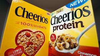Two types of Cheerios cereal, one with protein (R) and one without, are seen in this photo illustration in Wilmette, Illinois September 12, 2014. Protein has so far scored a big win for companies which are looking for new ways to beef up their profits as sales of traditional prepared foods slip and consumers seek healthier and fresher food options. General Mills, which Wednesday reported lower-than-expected quarterly profit, is counting on its protein-fortified snacks and expanded Yoplait Greek yogurt line to boost profits. It plans to expand distribution of its recently introduced Cheerios Protein, fortified with soy and pea protein, which at 26 cents an ounce costs significantly more than the 19-cents an ounce traditional oat Cheerios. Picture taken September 12, 2014. To match analysis USA-RETAIL/PROTEIN REUTERS/Jim Young (UNITED STATES - Tags: BUSINESS FOOD HEALTH)