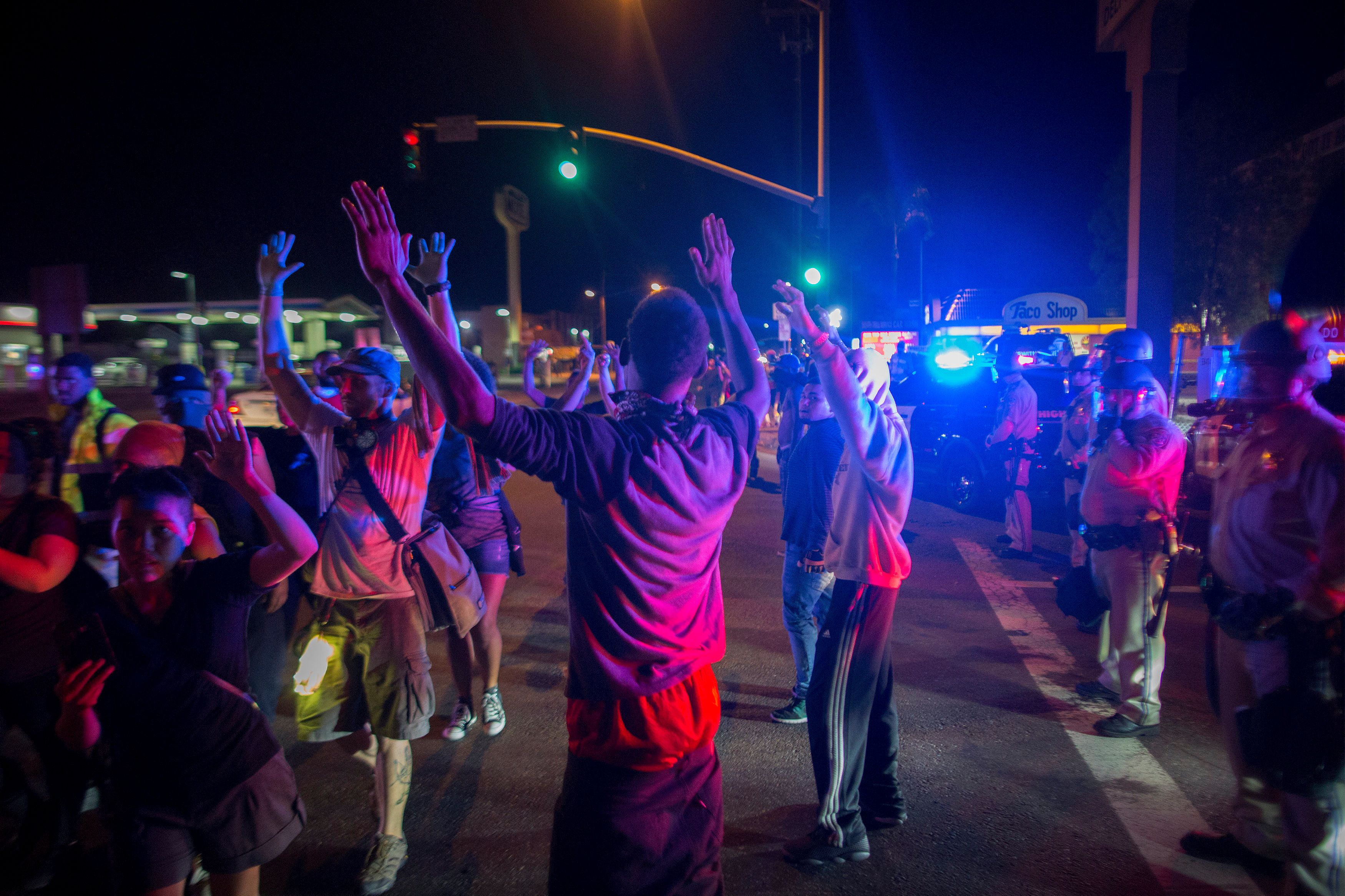 EL CAJON, CA - SEPTEMBER 30: Protesters raise their arms near a line of deputies in riot gear during march in reaction to the fatal police shooting of unarmed black man, Alfred Olango, on September 30, 2016 in El Cajon, California. The security detail consisted of members of The Black Panther Party, Nation of Islam and a coalition of black activist groups. A family member called police to help Olango as he was undergoing an emotional breakdown but shot him when he quickly pulled out an electronic cigarette device.  (Photo by David McNew/Getty Images)