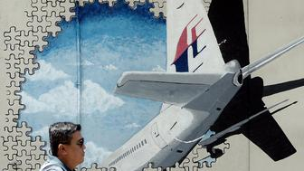 A Malaysian man walks in front of a mural of missing Malaysia Airlines MH370 plane in a back-alley in Shah Alam on March 8, 2016.  Malaysia and Australia said they remained 'hopeful' of solving the mystery of flight MH370 as the second anniversary of the plane's disappearance arrived March 8 with no end in sight for devastated families. / AFP / MANAN VATSYAYANA        (Photo credit should read MANAN VATSYAYANA/AFP/Getty Images)