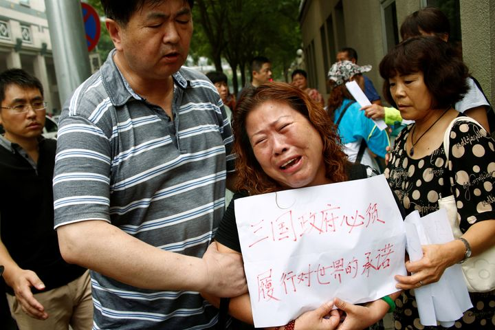 "A relative of one of the missing passengers holds a sign that reads: ""The three governments have an obligation to the world t"