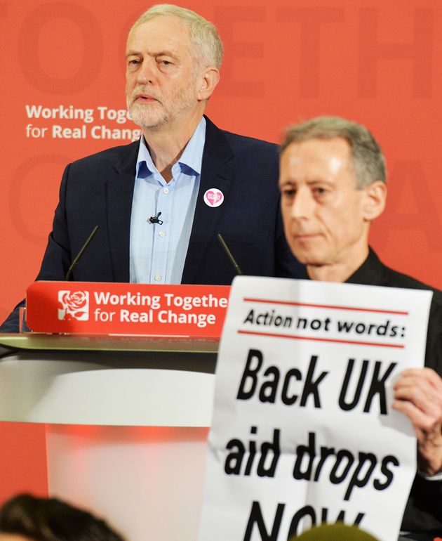 Corbyn (left) looks on as Tatchell (right) disrupts his speech in