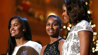 U.S. first lady Michelle Obama (R) and daughters Malia (L) and Sasha stand onstage during remarks by President Barack Obama for a taping of the Christmas in Washington television benefit program at the National Building Museum in Washington December 15, 2013. The 32nd annual Christmas in Washington show, benefiting the Children's National Health System, featured performers Hugh Jackman, Backstreet Boys, Sheryl Crow, Anna Kendrick, Janelle Monae and Pat Monahan.  REUTERS/Jonathan Ernst    (UNITED STATES - Tags: POLITICS ENTERTAINMENT)