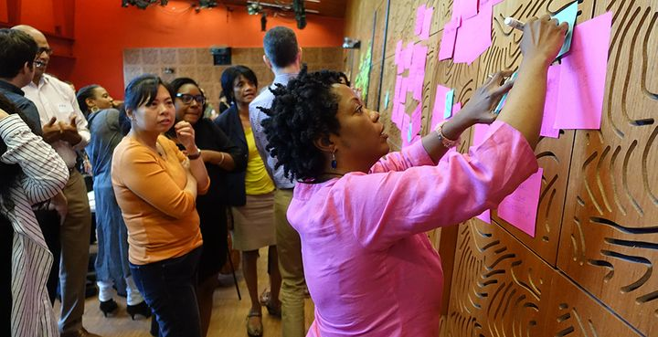 Melinda Weekes-Laidlow, a racial equity trainer with Race Forward, arranges sticky notes on a wall as she leads cultural advo