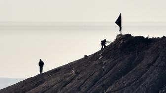 Alleged Islamic State (IS) militants stand next to a black IS flag atop a hill in at the eastern part of the Syrian town of Ain al-Arab, known as Kobane by the Kurds, as seen from the Turkish-Syrian border in the southeastern town of Suruc, Sanliurfa province, on October 7, 2014. Fresh air strikes by the US-led coalition hit positions held by Islamic State jihadists in the southwest of the key Syrian border town of Ain al-Arab (Kobane), according to an AFP journalist just across the border in Turkey. The strikes came a day after the extremists pushed into Kobane, seizing three districts in the city's east after fierce street battles with its Kurdish defenders. AFP PHOTO / ARIS MESSINIS        (Photo credit should read ARIS MESSINIS/AFP/Getty Images)