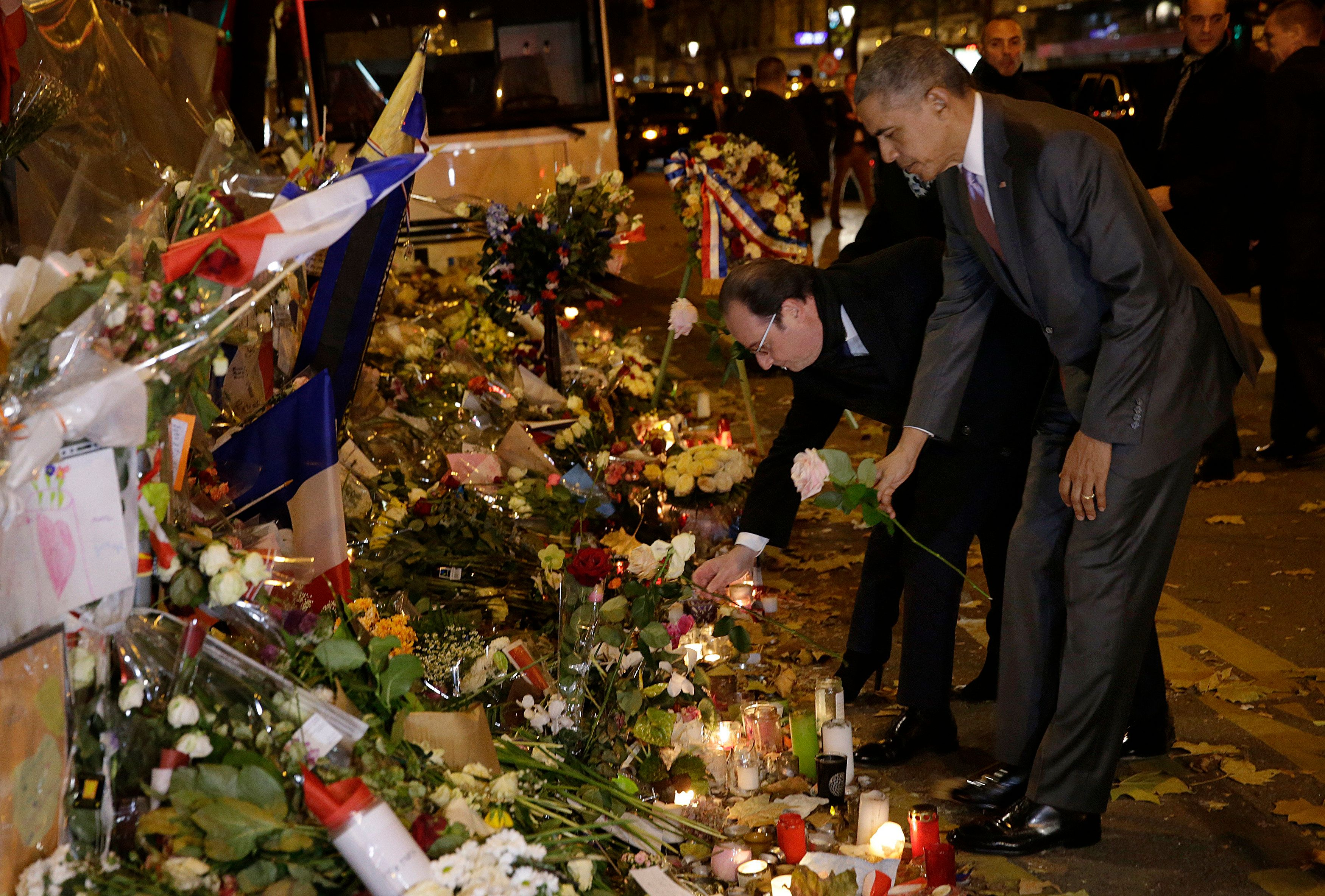 U.S. President Barack Obama and French President Francois Hollande pay their respect at the Bataclan concert hall, one of the recent deadly Paris attack sites, after Obama arrived in the French capital to attend the World Climate Change Conference 2015 (COP21), November 30, 2015.   REUTERS/Philippe Wojazer