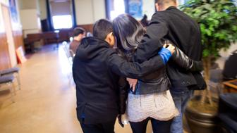 "Angela Navarro, an undocumented Honduran-born immigrant with a deportation order, embraces her husband and son after moving into West Kensington Ministry Church with her family, in Philadelphia, Pennsylvania November 18, 2014. Navarro, who has ""always lived in fear"" of deportation said on Tuesday she moved into a Philadelphia church as part of a national civil disobedience action aimed at pressing President Obama on immigration reform. Navarro is the ninth undocumented immigrant who has taken refuge in a church recently as part of what activists are calling the New Sanctuary Movement. Organizers offer sanctuary in churches because federal guidelines prohibit arrests in sensitive areas unless there is a threat to public safety or national security. REUTERS/Mark Makela (UNITED STATES - Tags: SOCIETY IMMIGRATION POLITICS RELIGION)"