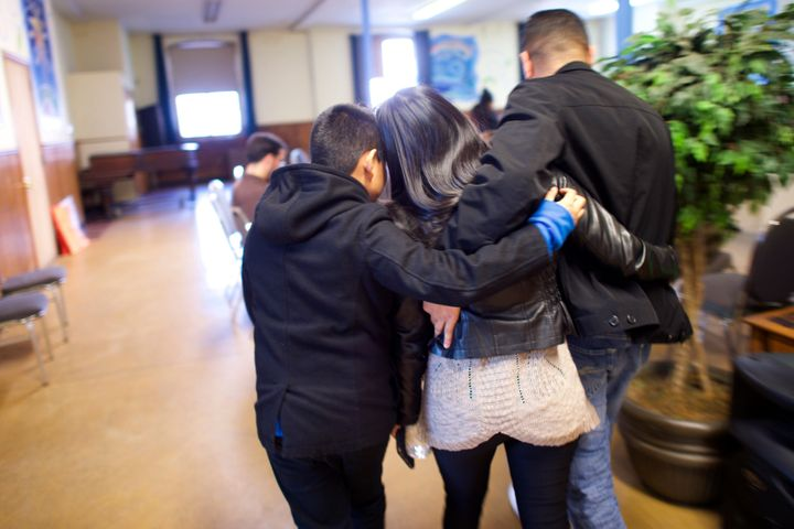 Angela Navarro, an undocumented Honduran-born immigrant with a deportation order, embraces her husband and son after moving i