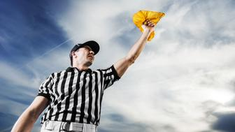A football referee holding a yellow flag against the sky.  He is calling the penalty.   http://dl.dropbox.com/u/40117171/sport.jpg