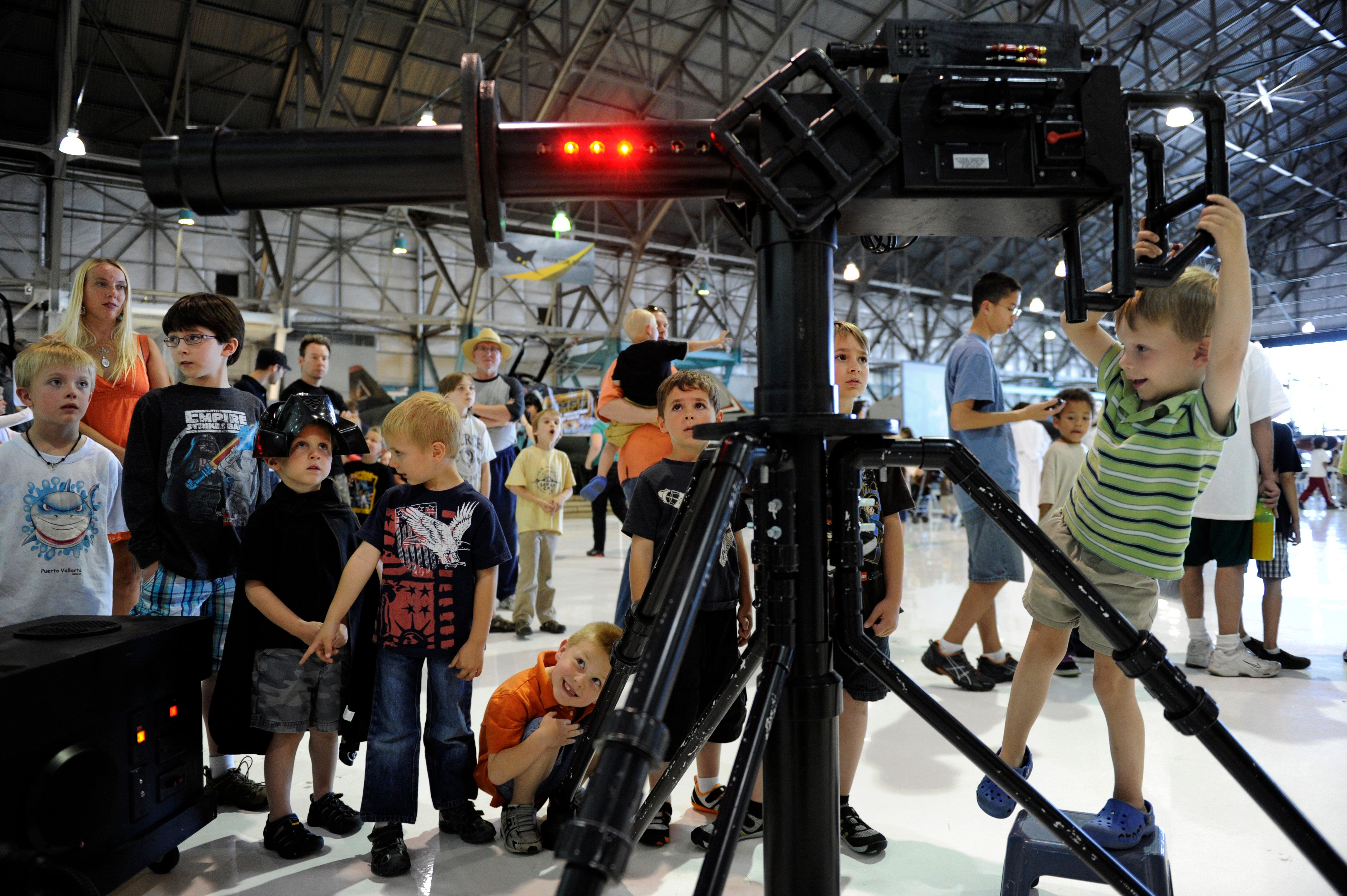 "Geoffrey Boden, 4, tries out a laser gun while visiting ""Star Wars at the Hanger"" at Wings Over the Rockies Air & Space M"