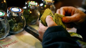 DENVER, CO. - DECEMBER 06: A tour members purchases marijuana at La Conte's Clone Bar & Dispensary during a marijuana tour hosted by My 420 Tours in Denver, CO on December 06, 2014. During the day tourists visited La Conte's grow facility, La Conte's Clone Bar & Dispensary, Native Roots dispensary  and Illuzions Glass Gallery.  (Photo By Craig F. Walker / The Denver Post)