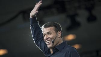 Motivational speaker Tony Robbins waves before speaking during the DreamForce Conference in San Francisco, California, U.S., on Tuesday, Oct. 4, 2016. Salesforce.com Inc. isn't wasting any time putting its new acquisitions to use in a bid to strengthen its business software against larger rivals such as Microsoft Corp. New products unveiled Tuesday will blend the company's services with Quip, the document company Salesforce purchased in August for about $600 million. Photographer: David Paul Morris/Bloomberg via Getty Images