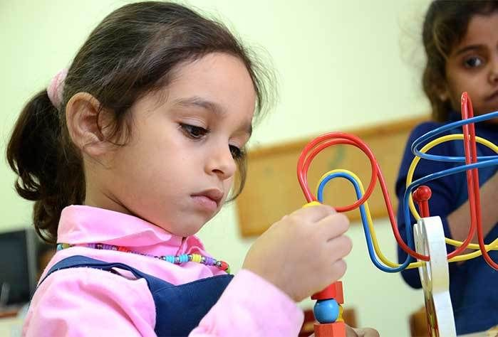 Palestinian preschooler exploring her new learning toy