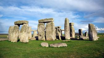 DSLR picture of the prehistoric monument of Stonehenge located in Wiltshire in England. The ring of standing stones is surrounded by green grass with a cloudy sky but sunny day of spring.