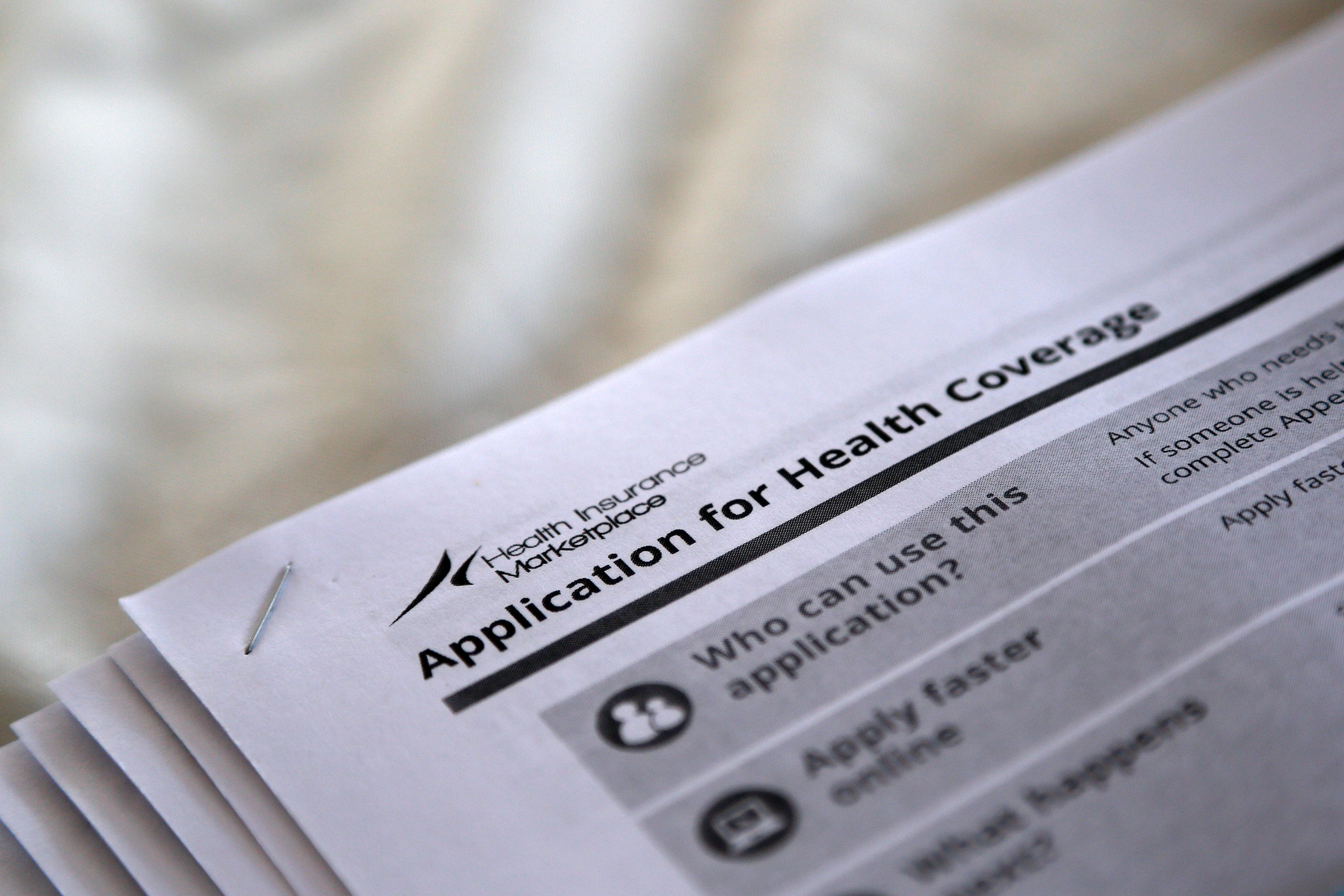 The federal government forms for applying for health coverage are seen at a rally held by supporters of the Affordable Care A