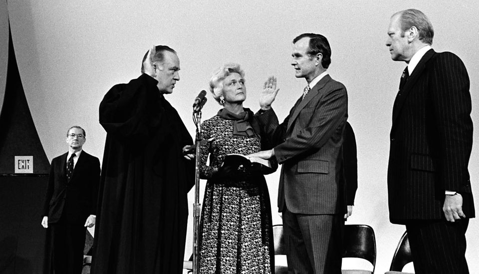 President Gerald Ford (far right) and Barbara Bush watch as Justice Potter Stewart swears in George H.W. Bush as director of