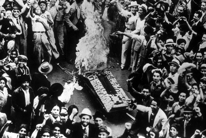 Crowds cheering as a coffin, representing an oil coffin, burns during celebrations in Mexico City of the government appropria