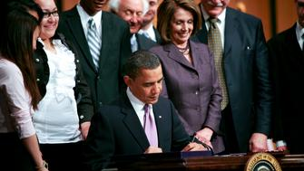 U.S. President Barack Obama signs the Health Care and Education Reconciliation Act of 2010 at Northern Virginia Community College with House Speaker Nancy Pelosi, a California Democrat at right in Arlington, Virginia, U.S., on Tuesday, March 30, 2010. Obama today signed the last piece of legislation to enact the U.S. health-care overhaul, a measure that includes changes to student aid programs. Photographer: Gary Fabiano/Pool via Bloomberg