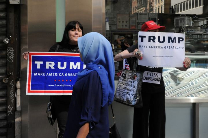 A woman walks past people holding U.S. Republican presidential nominee Donald Trump signs before the annual Muslim Day Parade