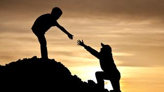 Concept image of two boys climbing a hill with one reaching out to help the other. Silhouette. Elementary age children. Side view. Teamwork concept. Additional themes include relationships, bonding, strength, hiking, climbing, outside, siblings, brothers, outstretched hand, partnership, friendship, care, help, assistance, and encouragement.
