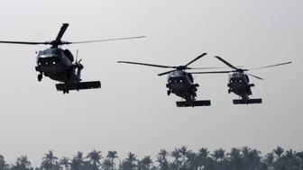 Three anti-submarine S-70C helicopters fly in formation during an annual drill at the Tsoying navy base in Kaohsiung, southern Taiwan, on January 18, 2017.   Taiwan on January 17 began two days of military drills simulating an attack by China as the government sought to reassure the public in the face of deteriorating relations with Beijing. / AFP / SAM YEH        (Photo credit should read SAM YEH/AFP/Getty Images)