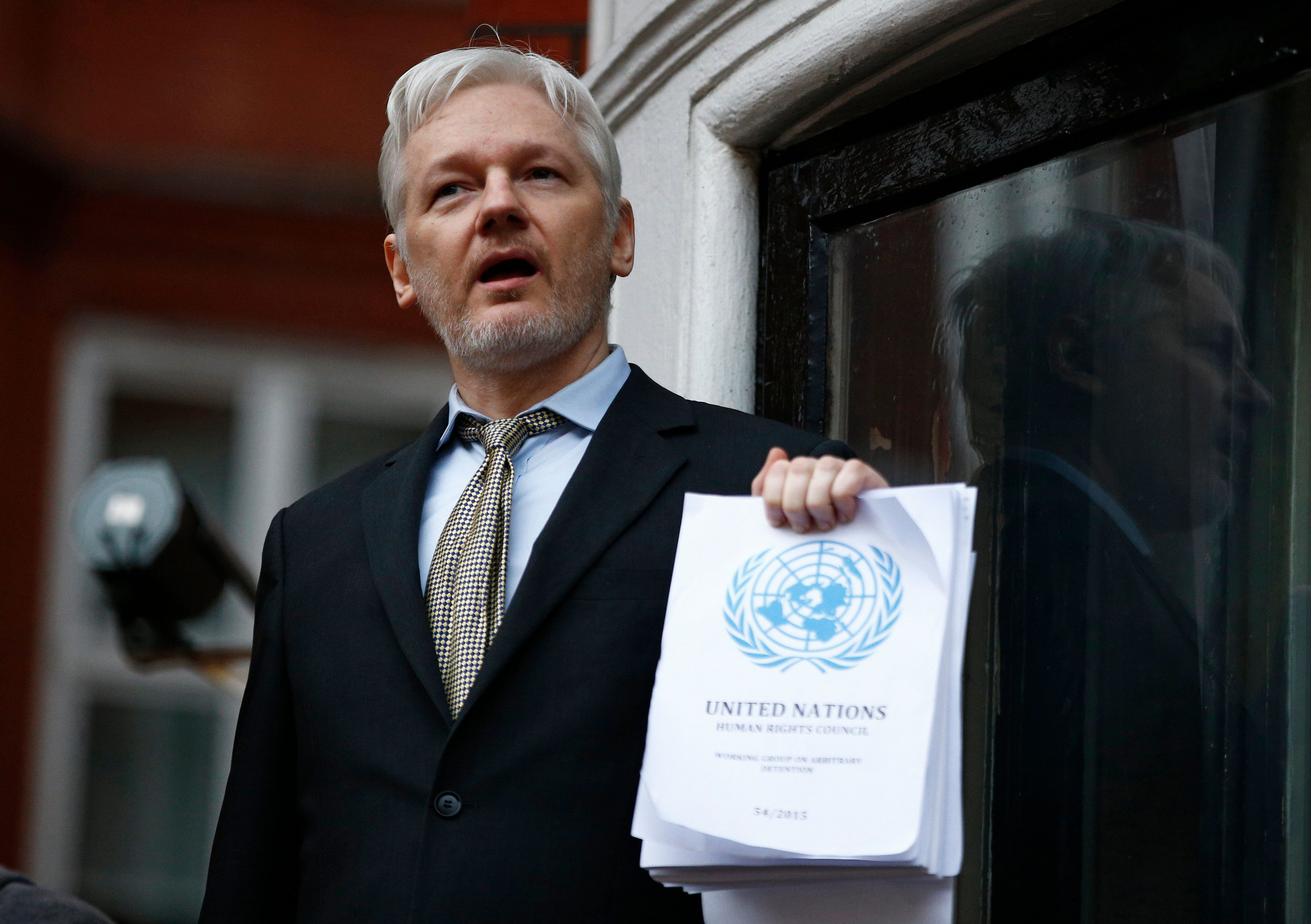 WikiLeaks founder Julian Assange holds a copy of a U.N. ruling that he should be allowed to go free the balcony of the E