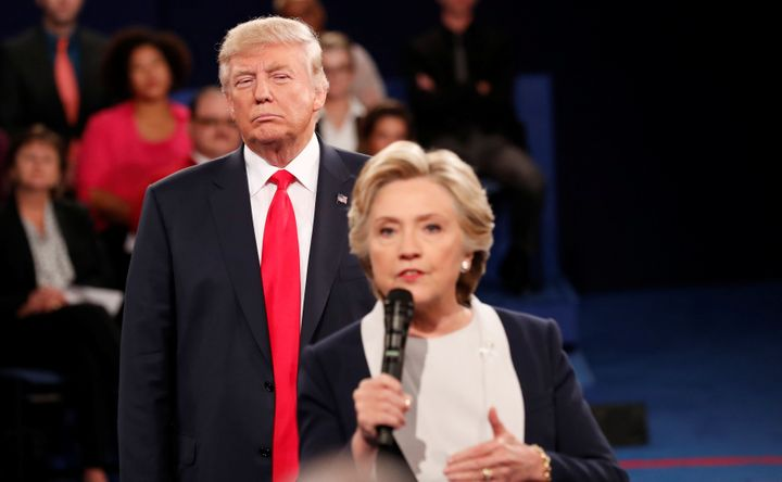 Trump listens as Hillary Clinton answers a question from the audience during their presidential town hall debate at St. Louis