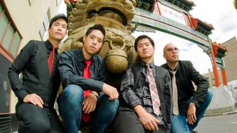 Portrait of Asian-American band The Slants (L-R: Simon 'Young' Tam, Ken Shima, Joe X Jiang, Tyler Chen) at the Old Town Chinatown gate, Portland, Oregon, USA on 21st August 2015. (Photo by: Anthony Pidgeon/Redferns)