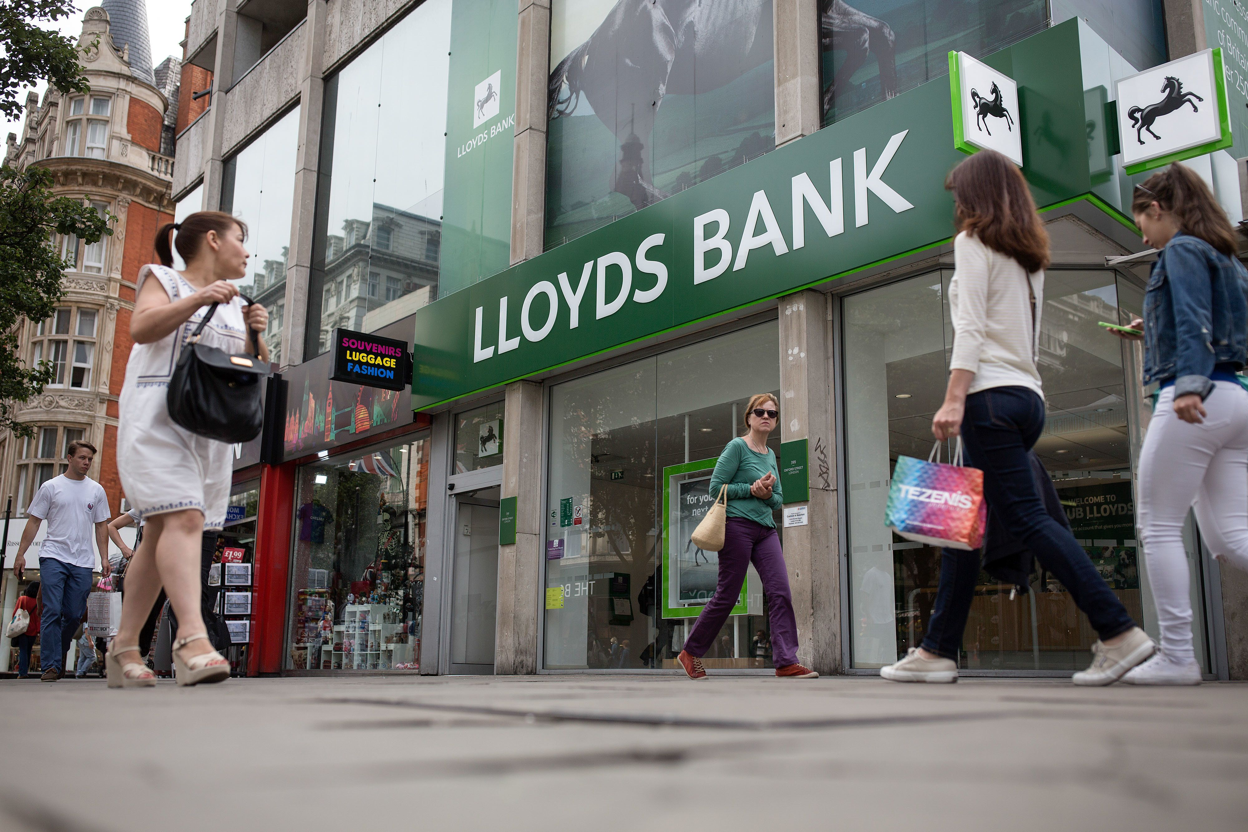 Pedestrians pass a Lloyds Bank branch, a unit of Lloyds Banking Group Plc, on Oxford Street in London, U.K., on Thursday, July 28, 2016. Lloyds Banking Group Plc will cut a further 3,000 jobs as it warned Britain's vote to leave the European Union would hurt its ability to boost dividend payments. Photographer: Simon Dawson/Bloomberg via Getty Images