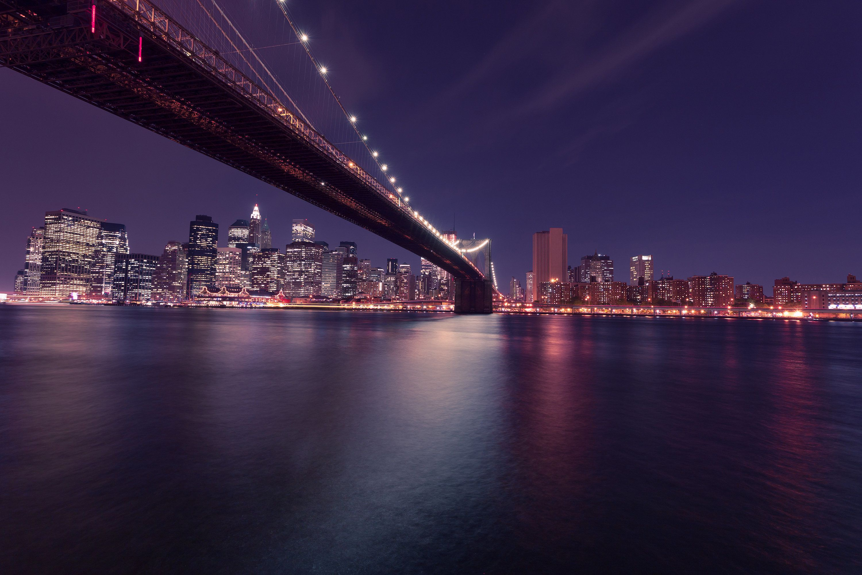 Dramatic New York City skyline with a cruise boat passing in the foreground. Beautiful New York City skyline at night. Lower Angle View of Manhattan and Brooklyn Bridge in New York at nighttime.