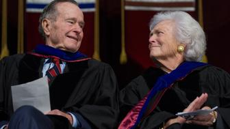 Former President George H.W. Bush and Barbara Bush listen as their son, US President George W. Bush, delivers the commencement address during the Texas A&M University graduation ceremony at Reed Arena in College Station, Texas, on December 12, 2008. AFP PHOTO/SAUL LOEB (Photo credit should read SAUL LOEB/AFP/Getty Images)
