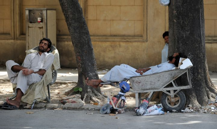 Pakistani day laborers rest by the side of the road as they wait for work in Islamabad on June 24, 2012. Rising unemployment