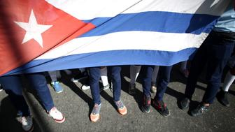 Mourners carry a Cuban flag as they head to Revolution Square for a massive tribute to Cuba's late President Fidel Castro in Havana, Cuba, November 29, 2016.         REUTERS/Alexandre Meneghini