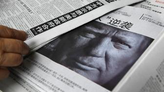 This photo taken on November 10, 2016 shows a newspaper featuring a photo of US President-elect Donald Trump at a news stand in Beijing.   Chinese media warned Donald Trump on December 12 that the one-China policy is 'non-negotiable' and dropping it could lead to Beijing supporting US enemies, after the president-elect said he might do so unless Beijing made concessions.  / AFP / Greg Baker        (Photo credit should read GREG BAKER/AFP/Getty Images)