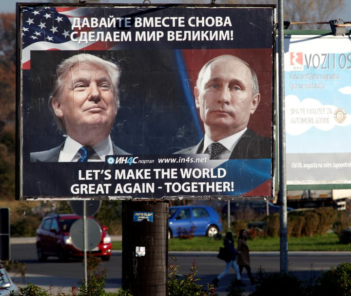 Pedestrians cross the street behind a billboard showing a pictures of US president-elect Donald Trump and Russian President V