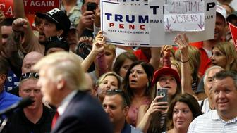 People hold up a sign claiming to be first time voters as Republican presidential nominee Donald Trump speaks onstage during a campaign rally in Akron, Ohio, U.S., August 22, 2016.   REUTERS/Carlo Allegri