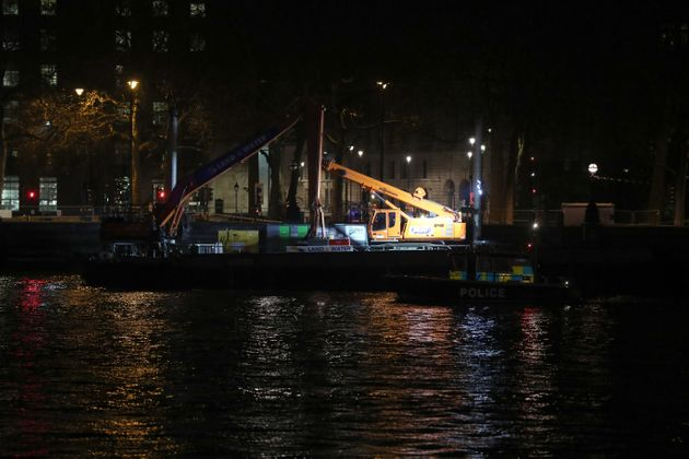 A police launch passes a barge moored on the River Thames in central London, as a suspected unexploded...