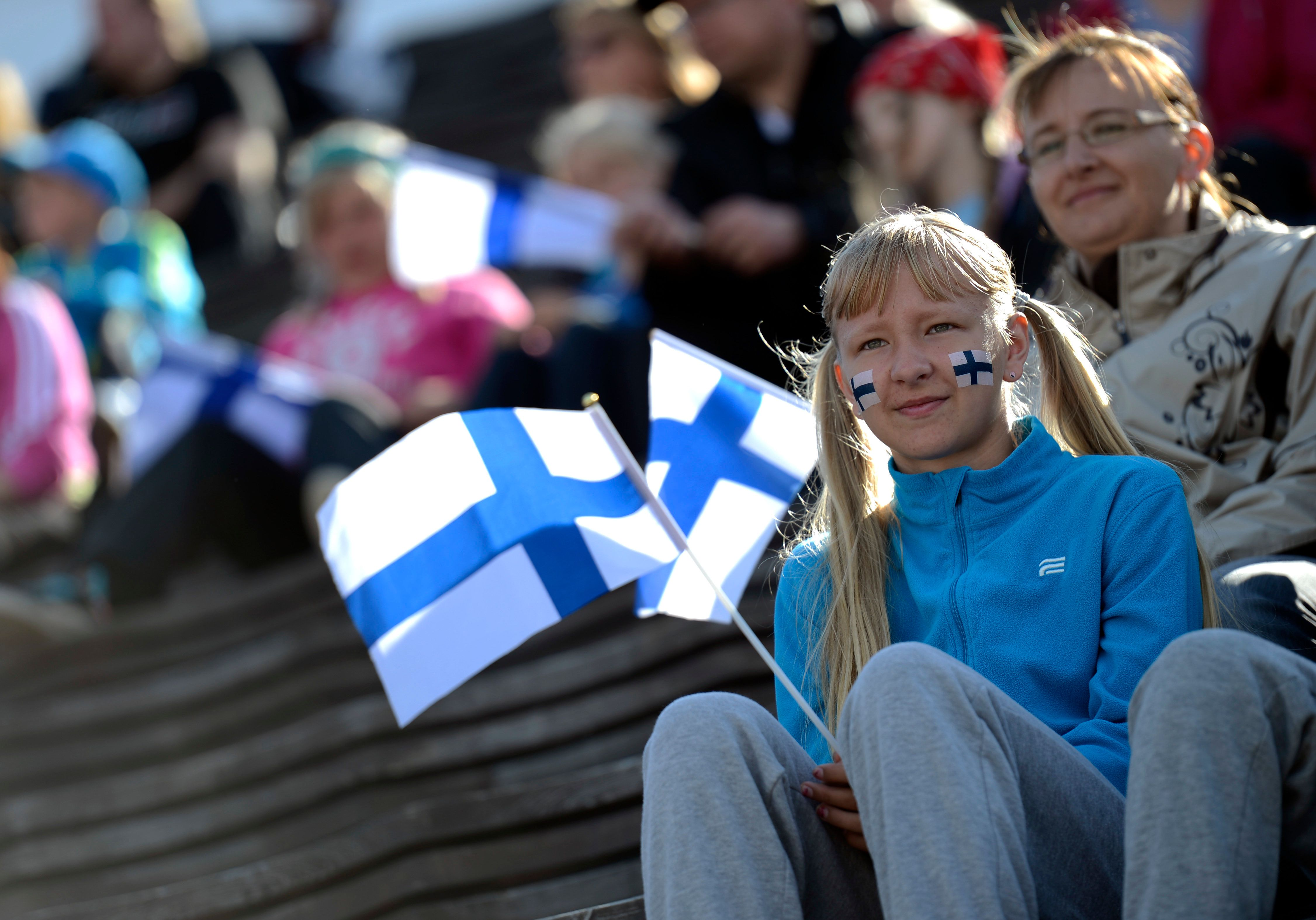 A girls hols a Finnish flag on the first day of the 2012 European Athletics Championships at the Olympic Stadium in Helsinki on June 27, 2012.  AFP PHOTO / JONATHAN NACKSTRAND        (Photo credit should read JONATHAN NACKSTRAND/AFP/GettyImages)