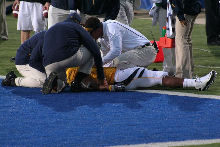 A player is examined for a concussion on the field.
