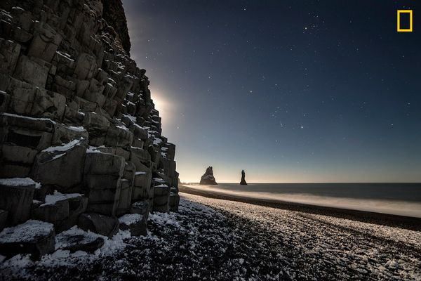 "<a href=""http://www.nationalgeographic.com/travel/top-10/top-beaches-world/"" target=""_blank"">Black sand</a> and towering"